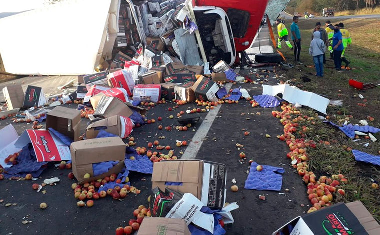 Motorista fica preso às ferragens após carreta carregada com frutas tombar na BR-040, em Sete Lagoas