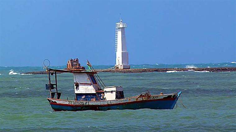 Entre o farol e a praia, os barcos dos pescadores