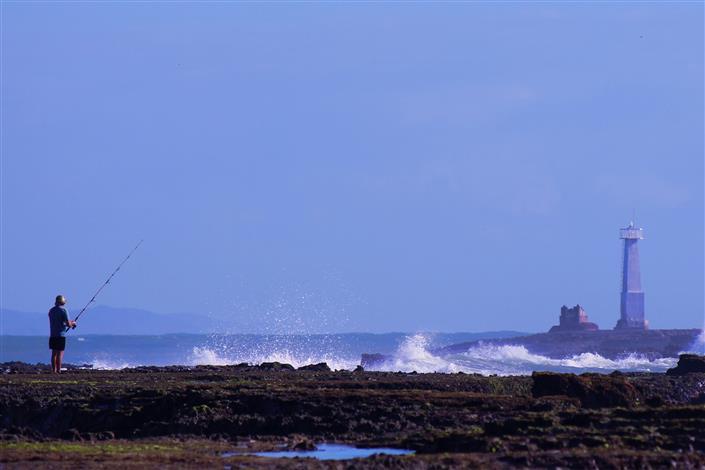 Perto da praia, o imponente farol no horizonte