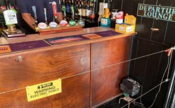 Pub instala cerca elétrica no balcão para garantir distância entre clientes
