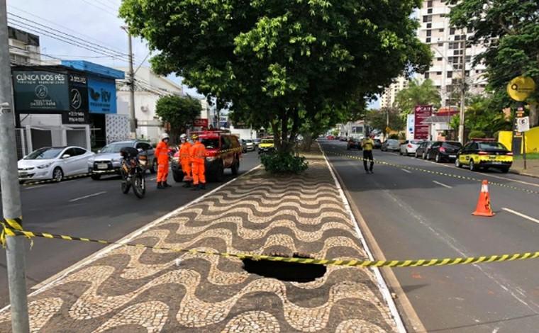 Calçada de canteiro central cede e jovem cai dentro de cratera em avenida de Uberlândia